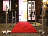 Barjerai su raudonu kilimu prie parduotuvės įėjimo.
