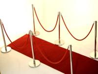 Grindų stovai su virvėmis ar juostomis ir raudonu kilimu.