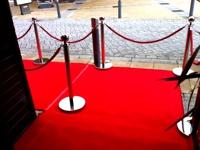 VIP praėjimas su atitvėrimais ir raudona kilimine danga.