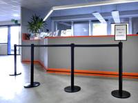 Keturių stovų eilių atitvėrimas su informacine lentele prie registratūros.
