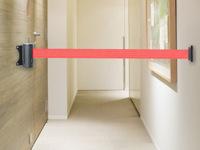 Praėjimą užtverianti ištraukiama juosta, kabinama ant sienos at plokštės.