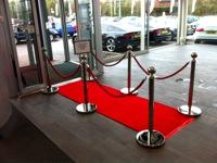VIP praėjimas su atitvėrimo stovais prie durų.