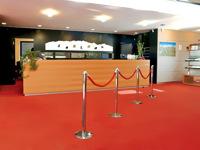 Informacijos laukiamasis atitvertas grindų stovais su virvėmis.