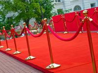 Barjerai su raudonu kilimu prie pagrindinio įėjimo.