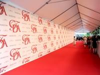 Ilgas koridorius su reklamine siena ir raudona kilimine danga.