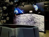 Mėnulio krateris už jo batutas ir foto siena.