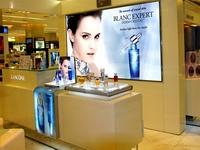 Parduotuvės interjeras su šviečiančiu reklaminiu stendu, vitrina