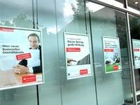 Popieriniai reklaminiai plakatai rėmeliuose prie vitrinos stiklo